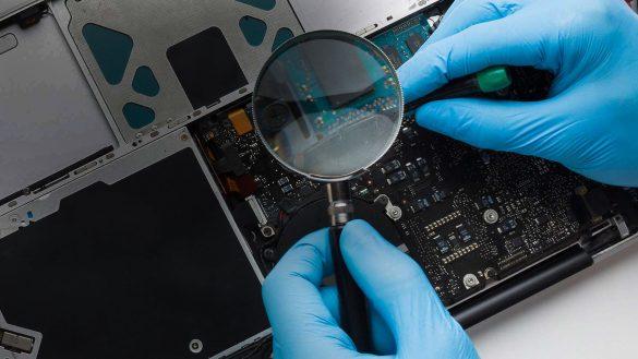 Mann repariert Laptop mit Lupe