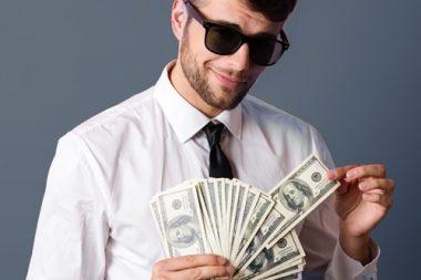 Bild Mann mit Sonnenbrille Geld in Hand